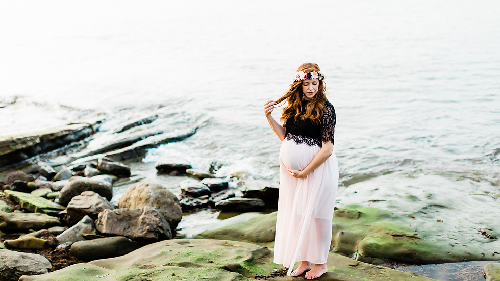 Pregnant woman with prenatal education holds her belly by the atlantic ocean in Sydney, Cape Breton, Nova Scotia, Canada