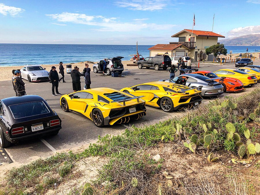 Lamborghinis, Porshes, and Mustangs at a beach in Malibu