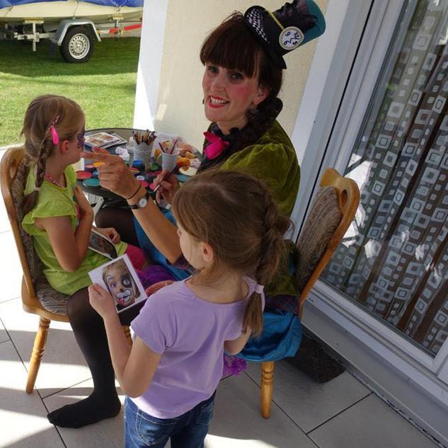 Die Hutmacherin bemahlt die Kinder auf einem Kindergeburtstag