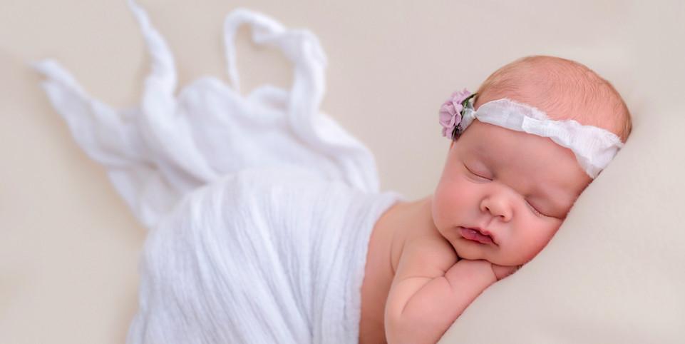 newborn-baby-inwhite-girl-flowers.jpg