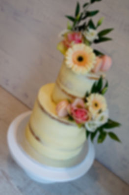Semi-naked wedding cake with fresh flowe