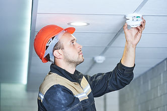 worker installing smoke detector on the