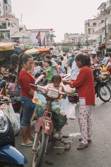 Women and baby in front of a street market