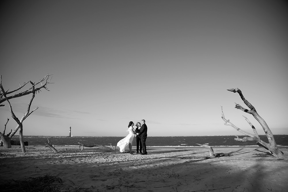 Couple exchanges their vows among driftwood trees on Folly Beach. Morris Island lighthouse is in the distance.
