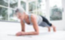 Mature woman doing pilates at home