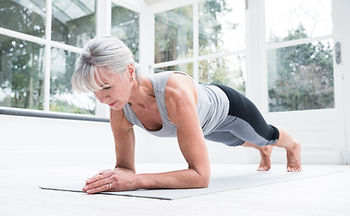 Mature woman doing pilates at home