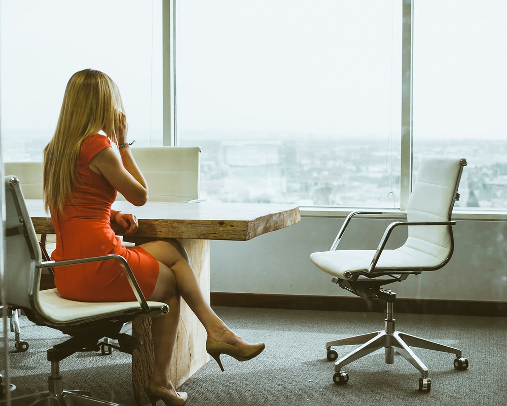 woman sitting in a swivel chair with legs crossed facing a huge glass window