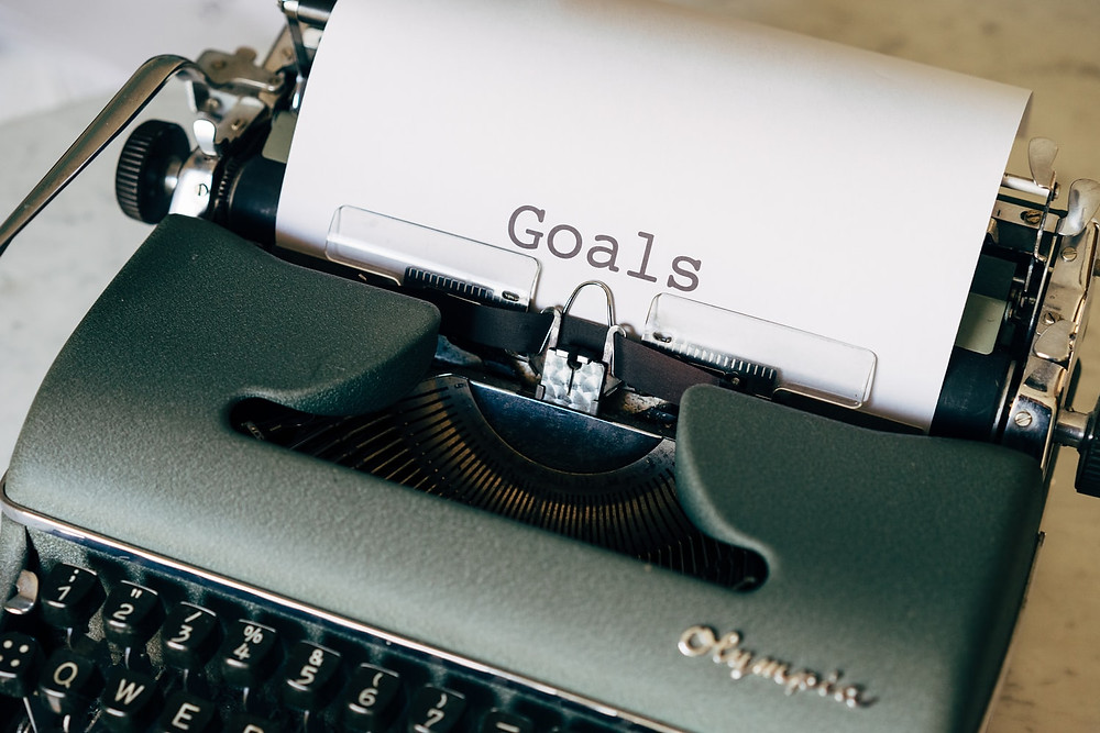 a paper with the word Goal written on it in a black typewriter