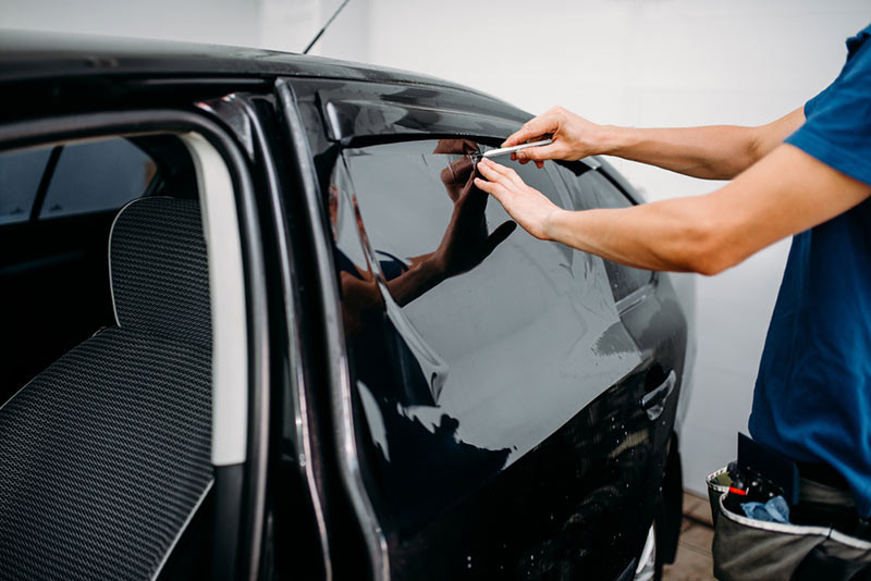 Image showing car window tinting film being applied from a blog post by Auto Wrap Centre Liverpool