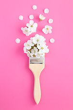 paintbrush-with-white-flowers-pink-surfa