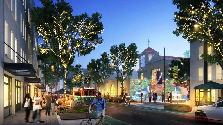 A rendering of Wynwood Norte neighborhood that includes lit trees, a streetcaqr, and a walkable urban environment