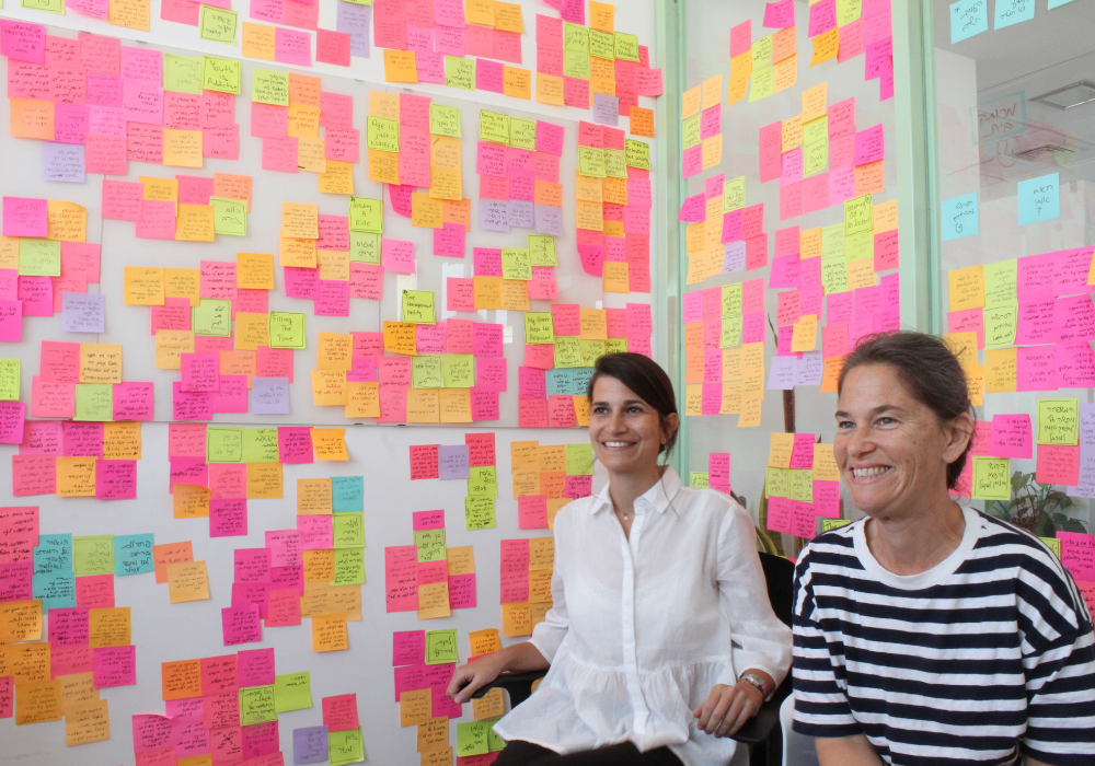 An image of two women sitting in front of a wall covered with colorful sticky notes