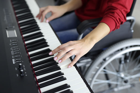 Woman in wheelchair is pressing piano ke