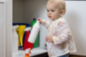 Toddler playing with household cleaners