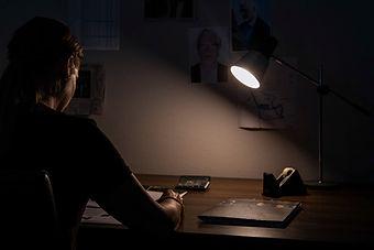 Person am Schreibtisch. Illustrationsfotografie Krimi