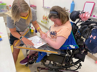 Volunteer helping women in wheel chair paint a picture