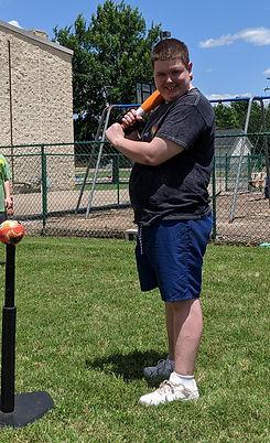 Smiling boy outside holding a baseball bat
