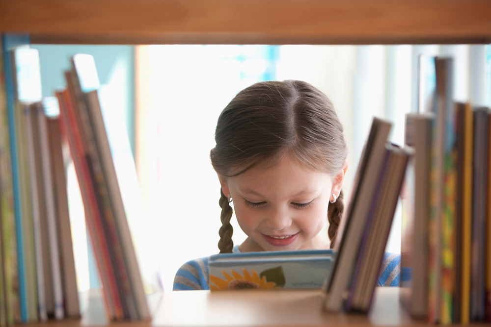 little girl with book as seen through a book shelf