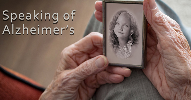 Speaking of Alzheimer's. Senior person holding a photo of a younger portrait.