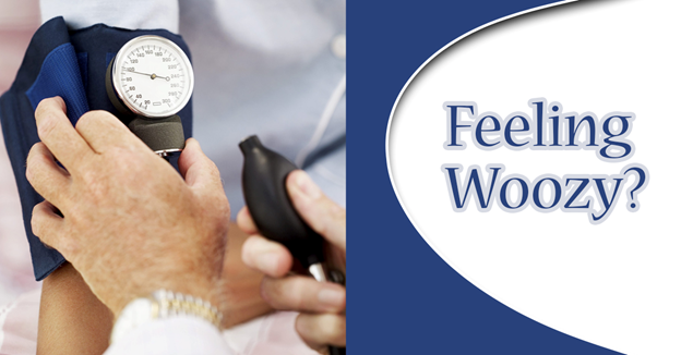 """Close-up of a physician's hand checking a patient's blood pressure using a blood pressure gauge with text """"Feeling Woozy?"""""""