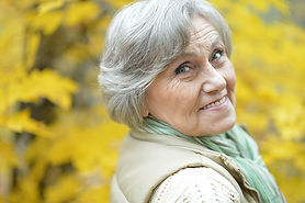 Picture of an older woman outside surrounded by yellow flowers