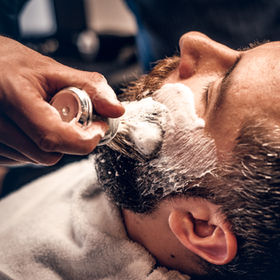 Barber applies shaving foam to a man's f