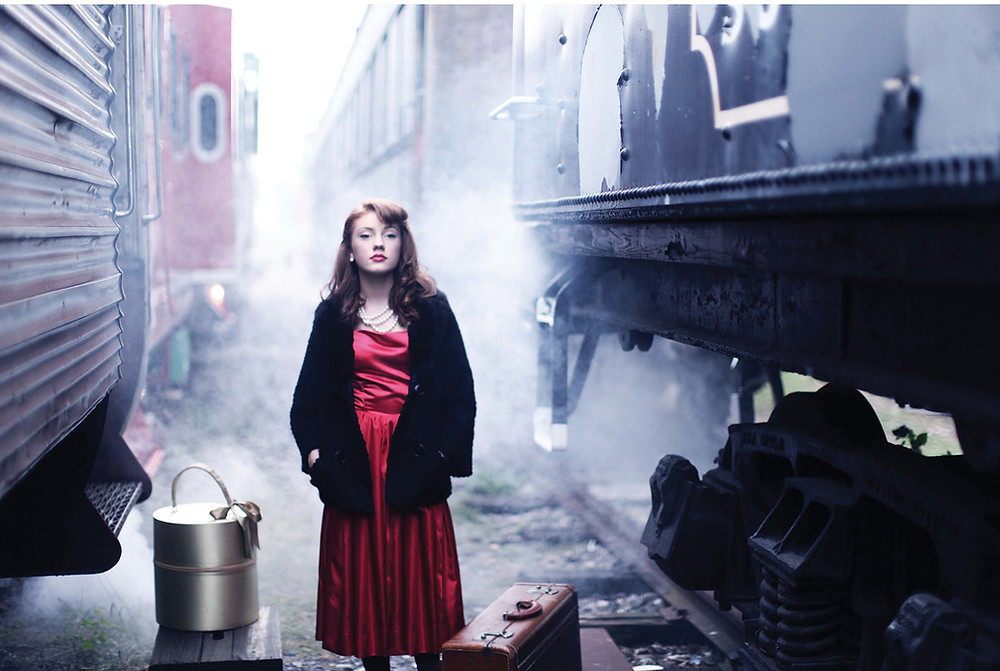young woman with victory roll bangs and a 1940s style waits in a smokey train yard between box cars with luggage