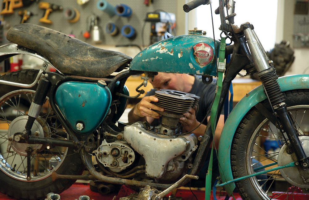 Man works on restoring his Harley Davidson MX250 (#49) in his garage