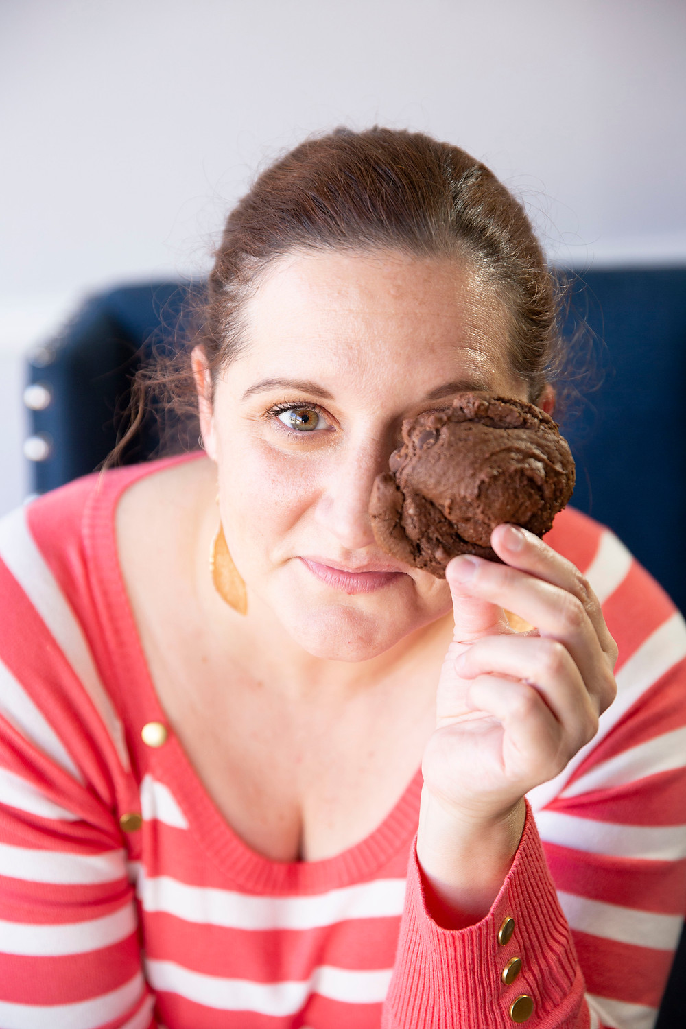 brunette woman holds chocolate cookie up to one eye