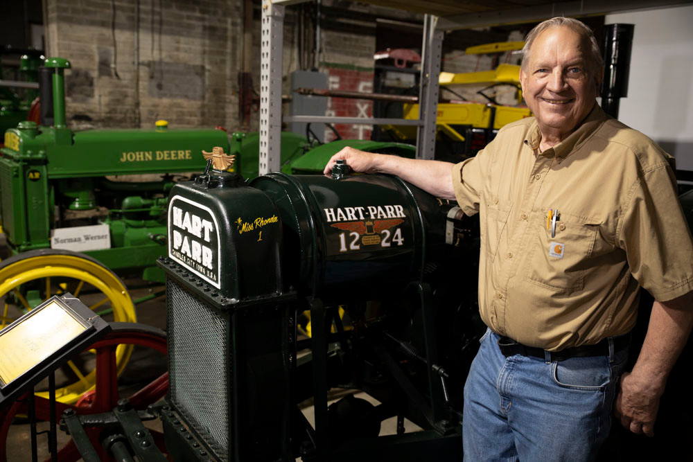 An older man stands by an antique Hart-Parr tractor at the American Tractor Museum
