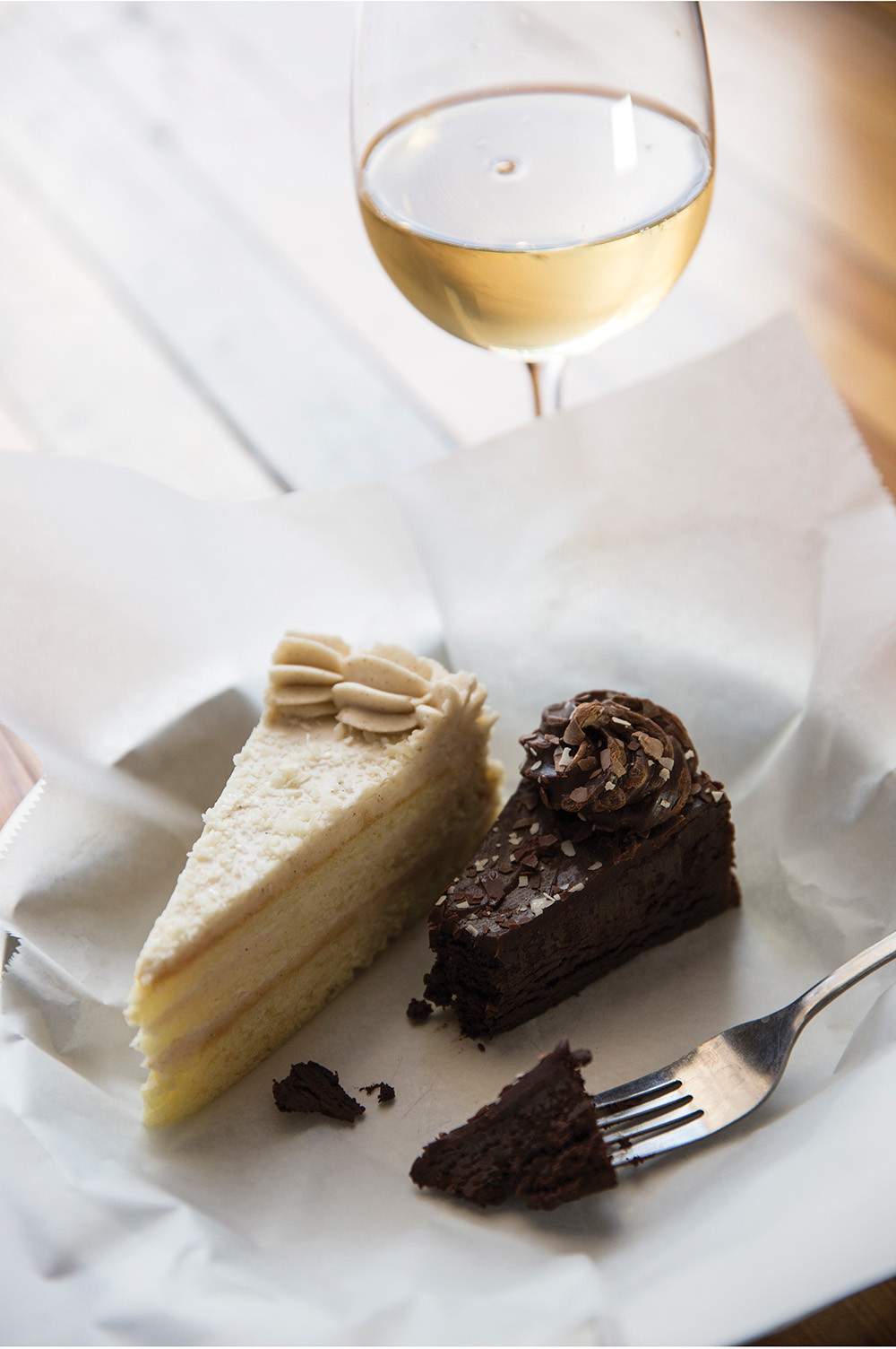 dessert for 2, one slice of cream cake, one slice of chocolate cake, with a glass of white wine