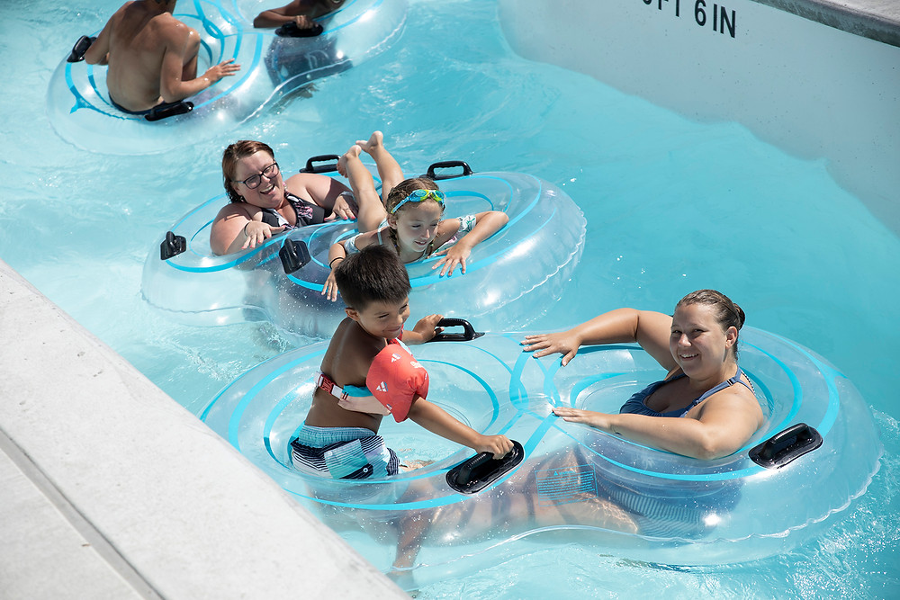 Happy and laughing families drift down the lazy river in double tubes at River Rapids Waterpark