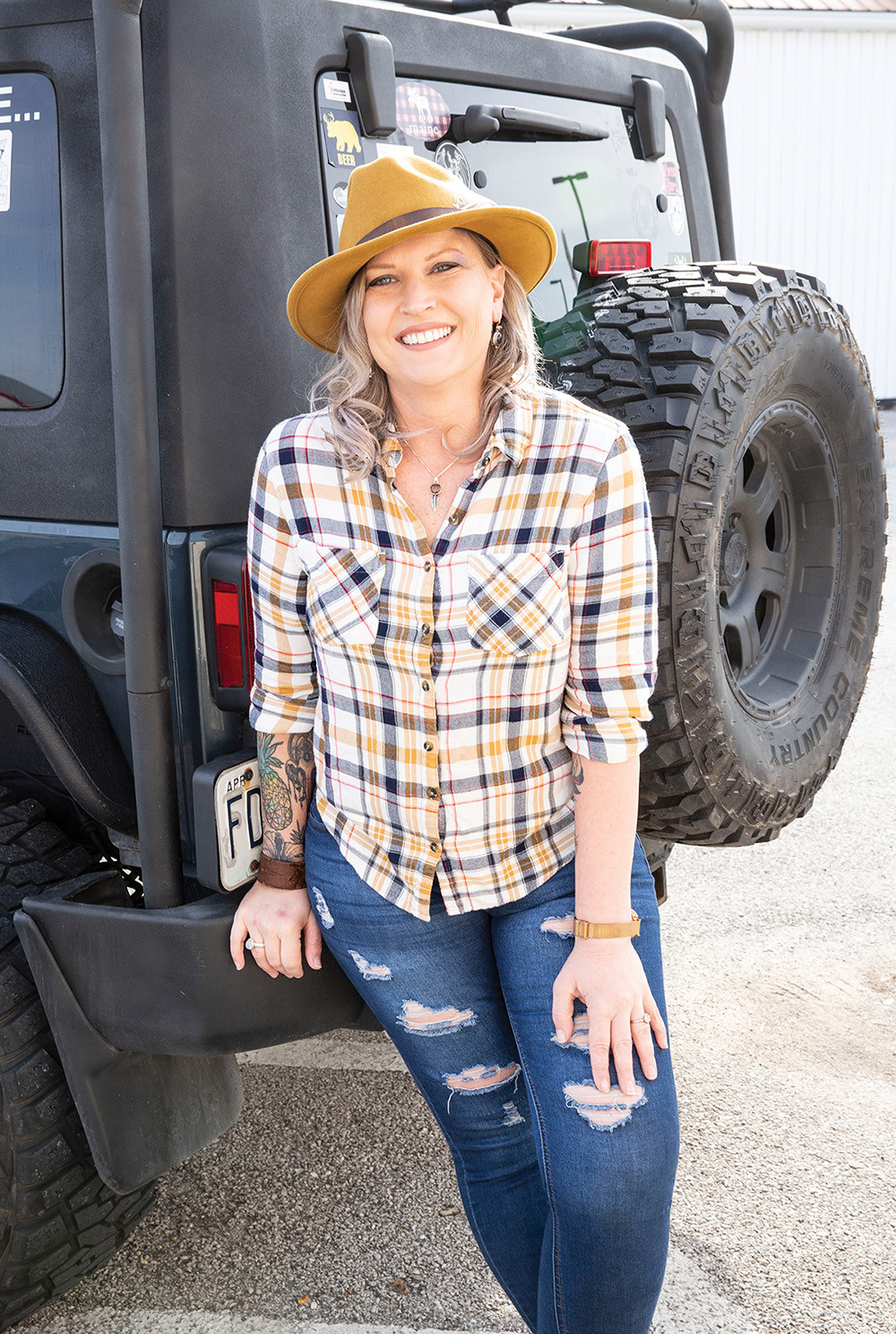 Beautiful woman in feathered fedora ripped jeans and flannel shirt leans against her jeep's spare and smiles