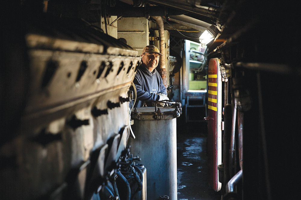 Engineer loos up at camera from down a long corridor lines with pipes and machines in train engine