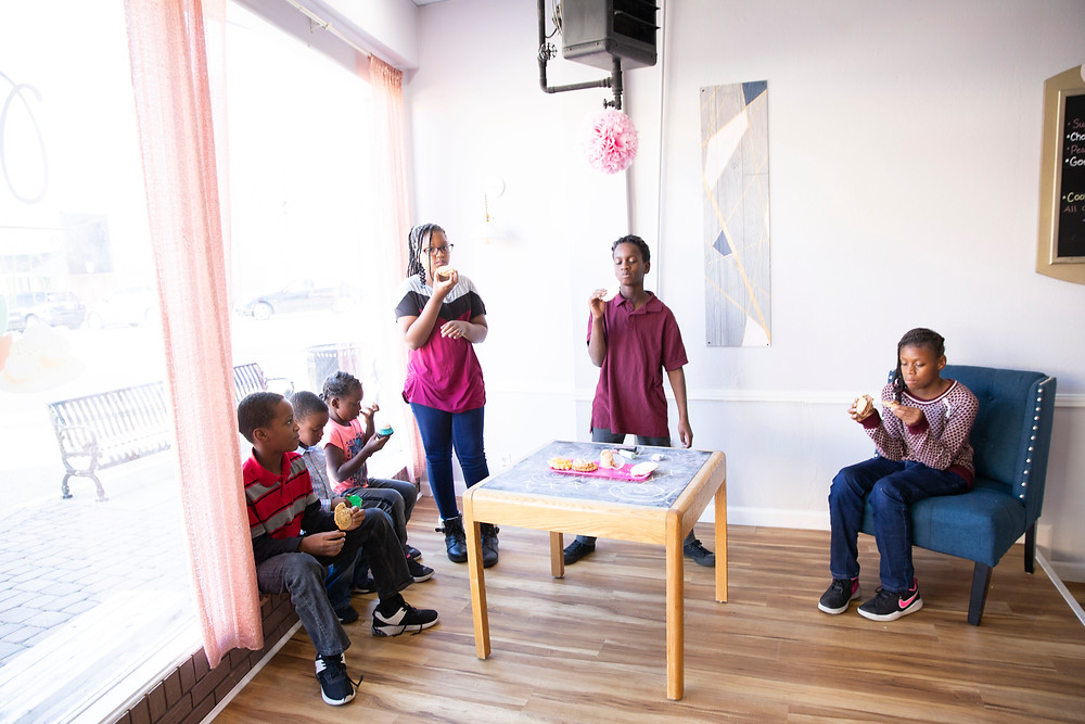 6 children boys and girls enjoy eating cookies in an open room with a large front window