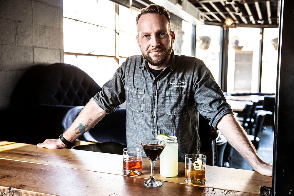 Young man leans on table behind 4 bourbon cocktails he created