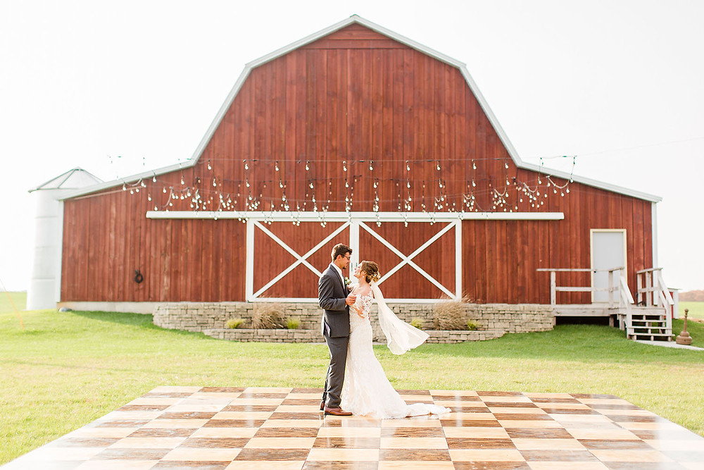 bride and groom dancing on outdoor dance floor with twinkle lights above at The Barn at Lone Eagle Landing wedding venue