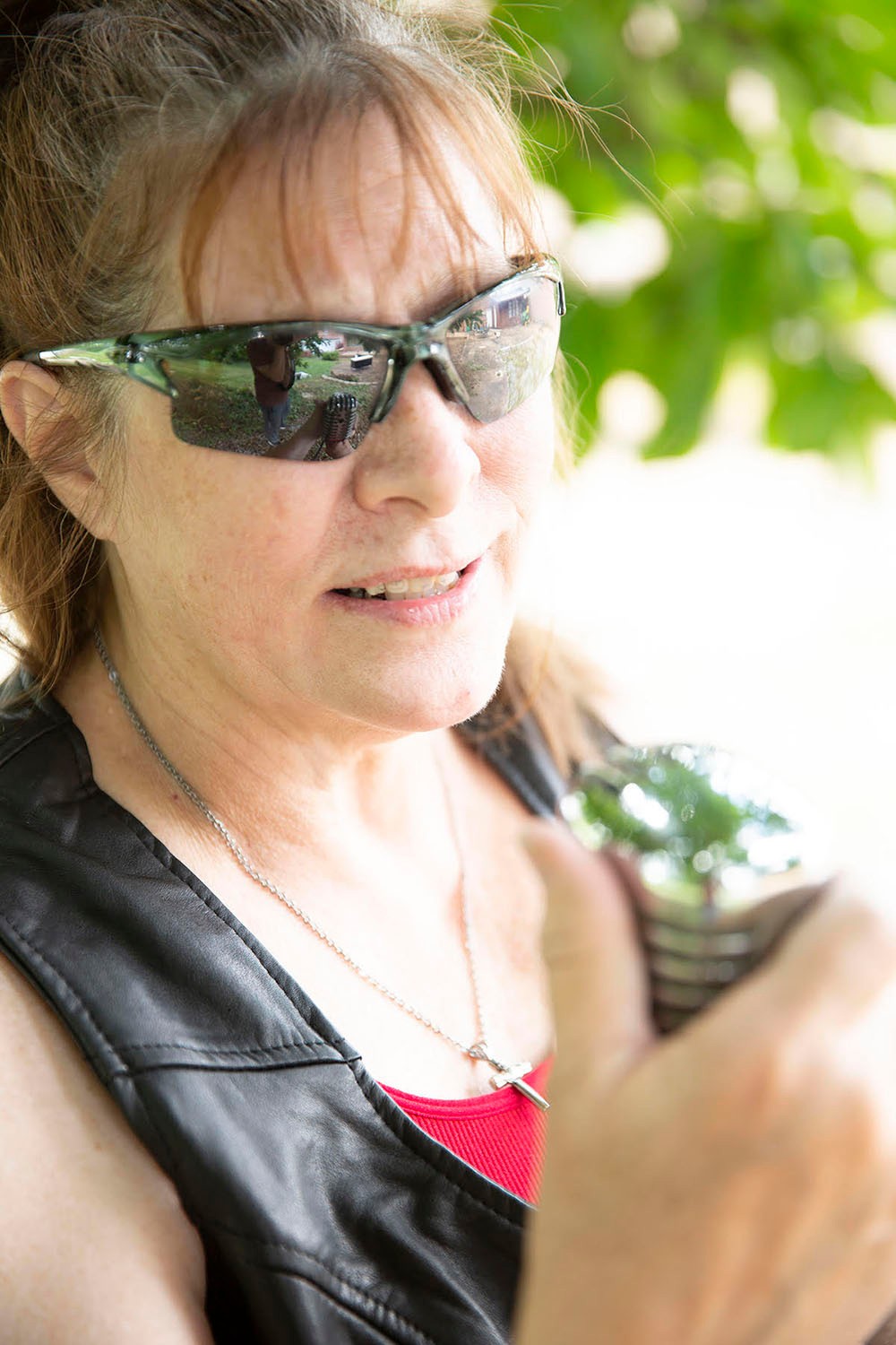 brunette woman with sunglasses smiles and holds a classic chrome microphone under a large tree