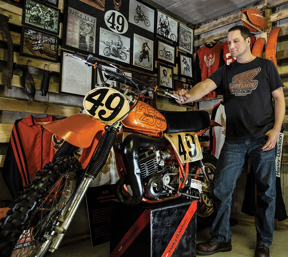 A man holds the handlebar of a Harley Motocross MX250 (#49) looking at it fondly in his garage decorated with #49 memorabilia