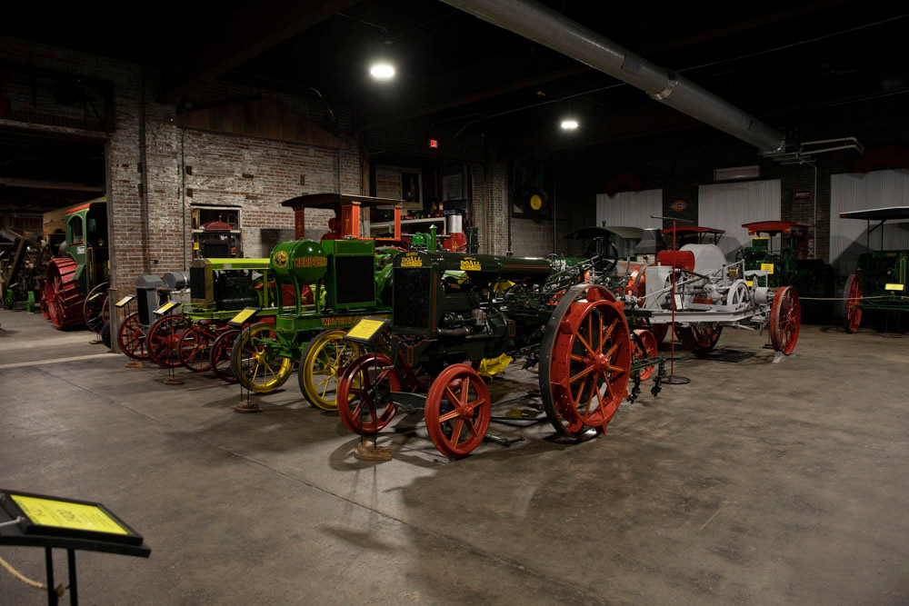 A large collection of brightly colored beautifully restored antique tractors at the American Tractor Museum