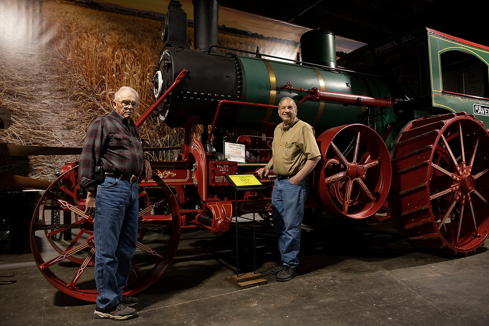 2 older gentlemen stand in front of a huge antique steam engine tractor that looks much like an old train