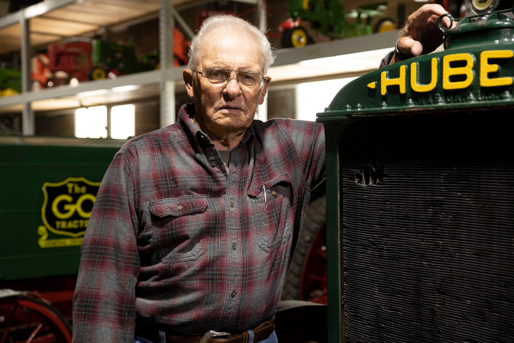 An old gentleman with spectacles and a flannel shirt poses with an antique Huber tractor at the American Tractor Museum