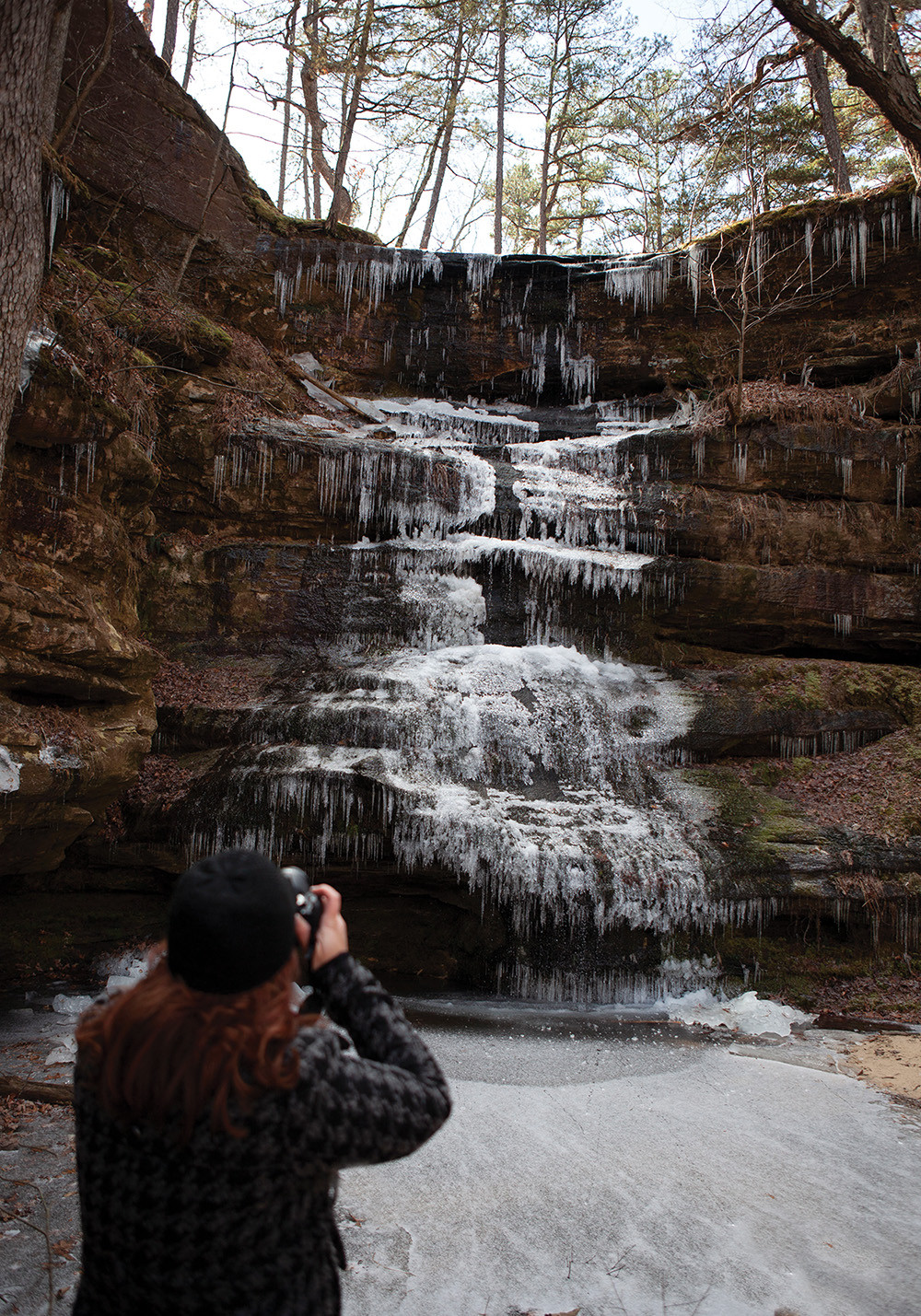 young woman snaps a picture of a frozen waterfall and creek at Hickory Canyon