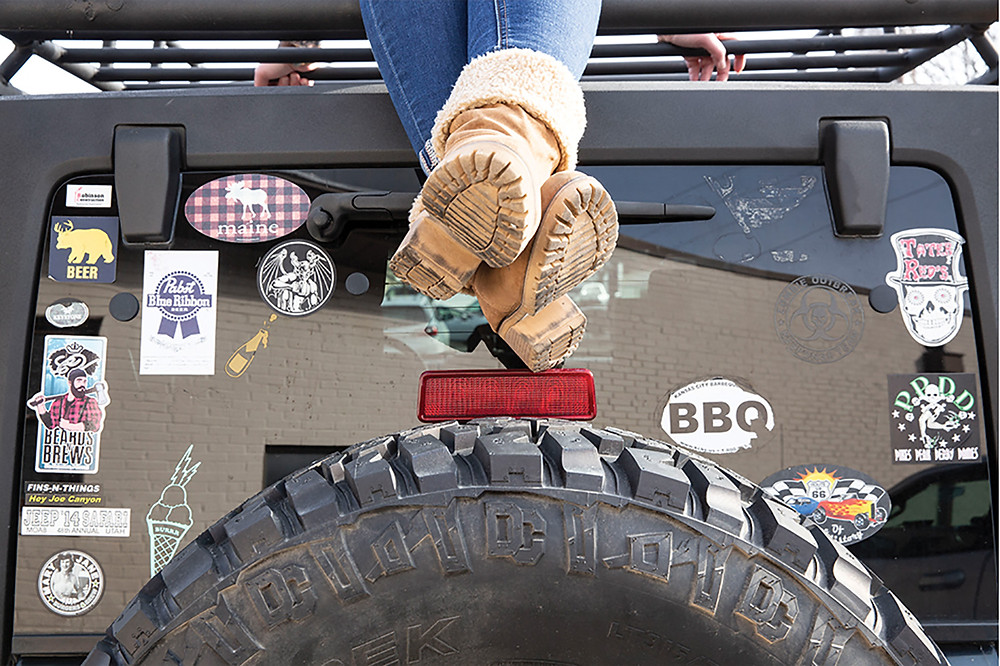 Carisa's legs dangle from the top of her jeep above the spare tire in front of a sticker covered back glass crossed at her fur topped hiking boots