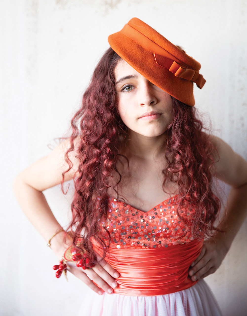 Young girl in evening gown with wildly curly hair under a vintage hat, portrait