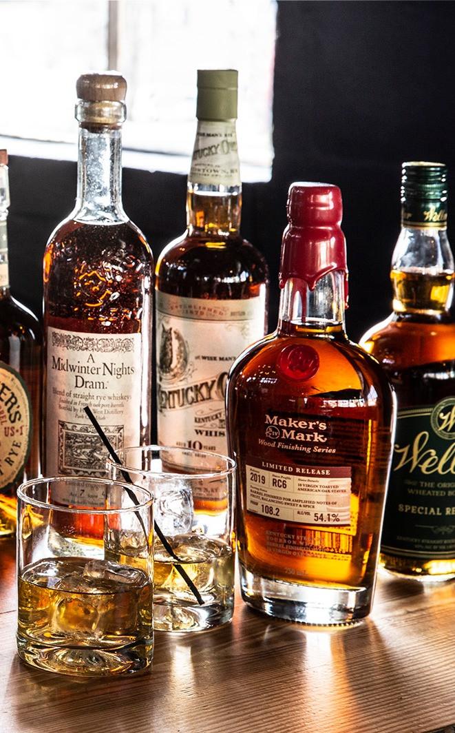 Multiple bottles of bourbon of varying sizes behind 2 glasses of whiskey on the rocks