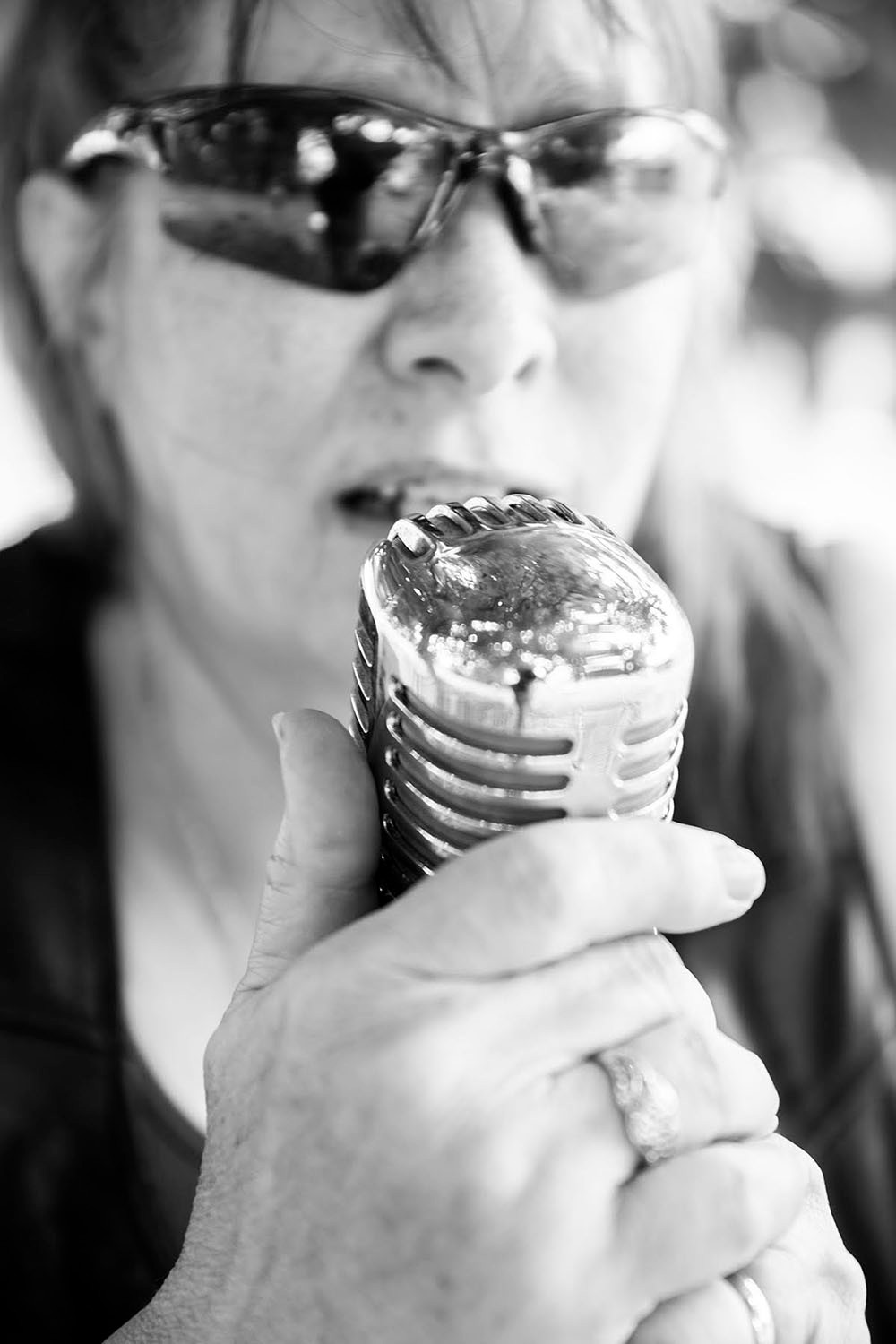 woman with sunglasses sings into classic chrome microphone