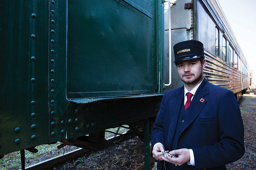 young man in a conductor hat and jacket checks his pocket watch by the train