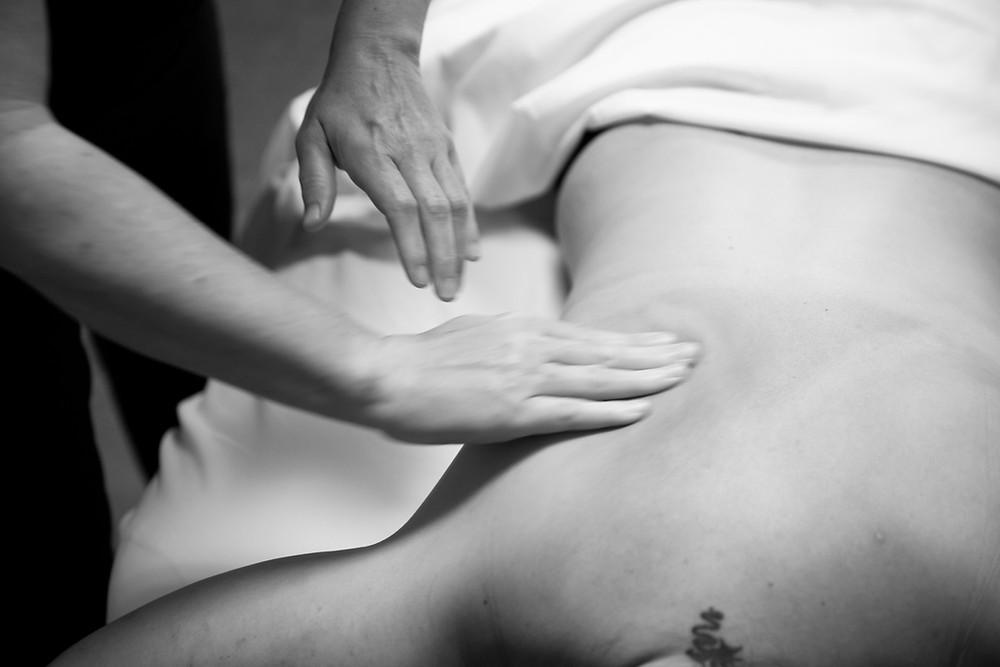gentle hands massage a tanned tense back at Massage & Skin Works in Farmington