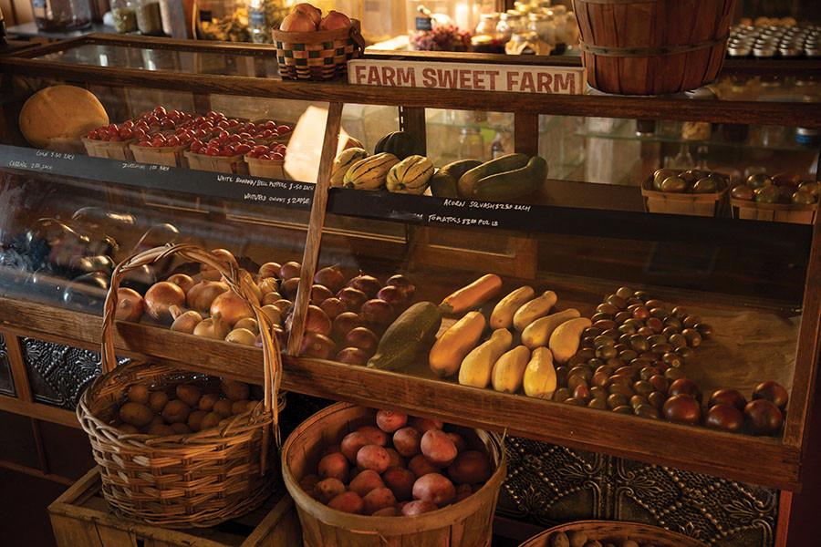 display case full of fresh seasonal produce baskets of potatoes and a sign reading Farm sweet Farm